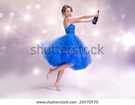 Photo of young brunette holding up a bottle of champagne - stock photo