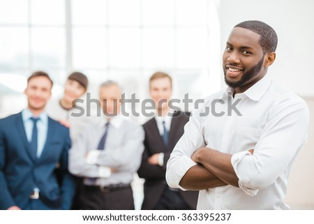 Photo of young businessman and his colleagues. Businessmen and business woman working in office with big window. Men and woman smiling and looking at camera - stock photo
