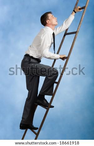 Photo of young businessman climbing upwards upon ladder - stock photo