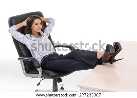 Photo of young businesswoman wearing suit. She sitting with her feet on desk and holding hands behind head. Isolated on white background - stock photo