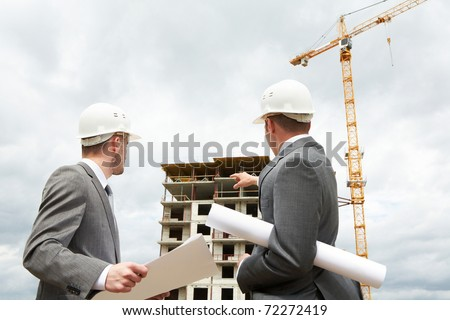 Photo of young engineer showing something to his partner at building site - stock photo