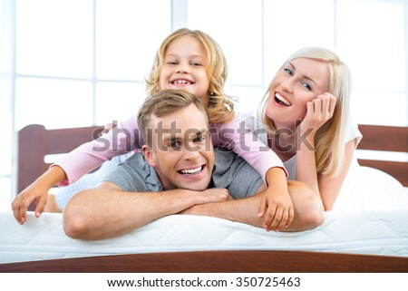 Photo of young family of three lying on nice white bed. Young family demonstrating quality of mattress - stock photo