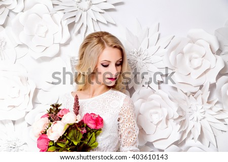 photo of Young gorgeous woman, bride, blond long curly hair, studio decoration, white dress, flowers, - stock photo