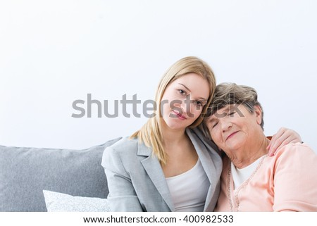 Photo of young granddaughter helping ill grandmother - stock photo