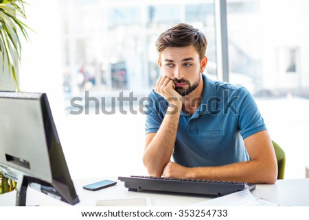 Photo of young, handsome, successful and confident businessman. Young businessman is bored while working with computer. White modern office interior - stock photo