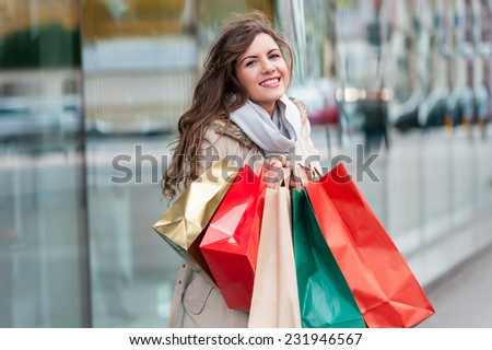 Photo of young joyful woman with shopping bags on the background of shop windows. Outdoors. - stock photo