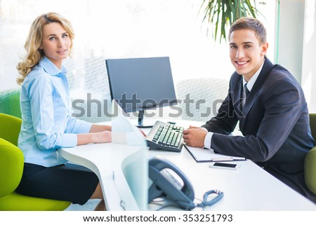 Photo of young male consultant and female buyer. Young woman buying new car in auto show. Signing of contract. Concept for car rental - stock photo