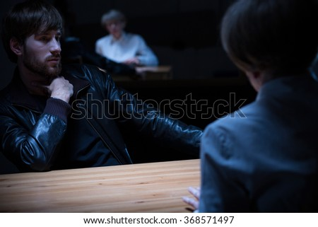 Photo of young man interrogated on police station - stock photo