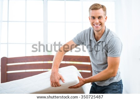Photo of young man standing near nice white bed. Young man demonstrating quality of mattress - stock photo