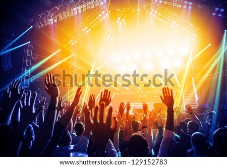 Photo of young people having fun at rock concert, active lifestyle, fans applauding to famous music band, nightlife, DJ on the stage in the club, crowd dancing on dance-floor, night performance - stock photo