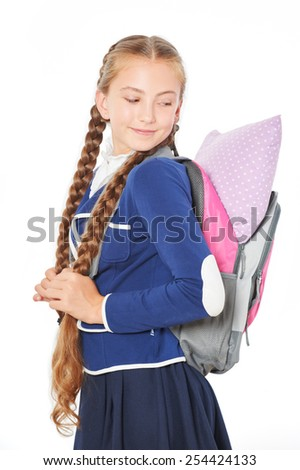 Photo of young school girl keeping pillow in her bag. Isolated on white background. Concept for sleepiness at school lessons - stock photo