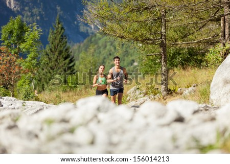 Photo of young sporty couple doing running in the mountains - stock photo
