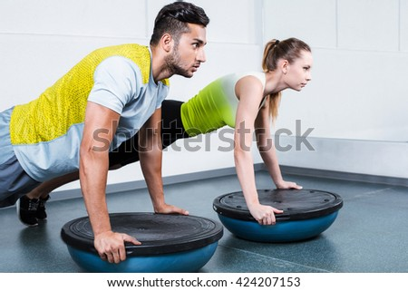 Photo of young sporty woman and man. Fitness people working out with bosu at fitness club - stock photo