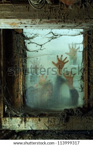 Photo of zombies outside a window that is covered with spiderwebs and filth. - stock photo