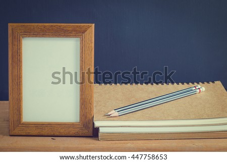 Photo old wood frame with book and 2 pencil on old wooden table, black background. Emphasizing copy space for write text. image style vintage. - stock photo