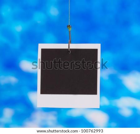 Photo on fish hook on blue background - stock photo