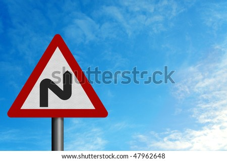 Photo realistic metallic reflective 'double bend' road sign, against a background of a bright blue summer sky. With space for your text / editorial overlay - stock photo