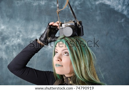 Photo session of the pretty young blonde girl with green hair in the steampunk style with photo camera - stock photo
