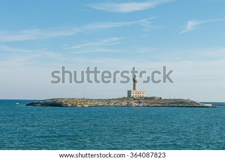 Photo shows old lighthouse on small island surrounded by blue sea. - stock photo