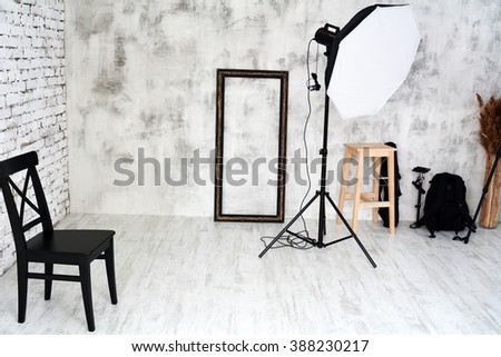 Photo Studio in a white room with brick wall, with a chair, reflector  - stock photo
