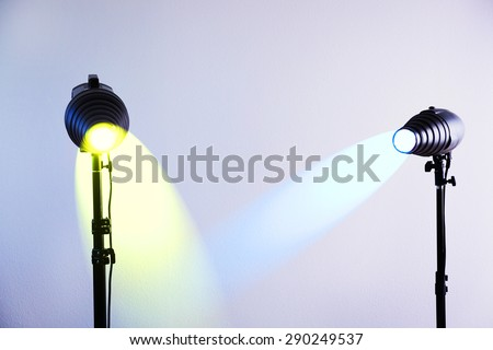 Photo studio with lighting equipment on grey wall background - stock photo
