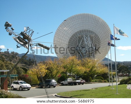 Photo taken at Tidbinbilla Deep Space Complex near Canberra in the Australian Capital Territory featuring a radiotelescope dish and a model of the Voyager Space Probe. - stock photo