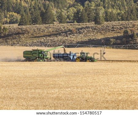 Photo taken in east Idaho of combine and tractor working grain harvest. - stock photo