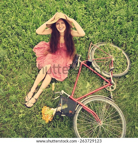 photo with artistic effect. vintage toning. film retro style. young woman in a hat with a bike in the park . Active people. Outdoors - stock photo