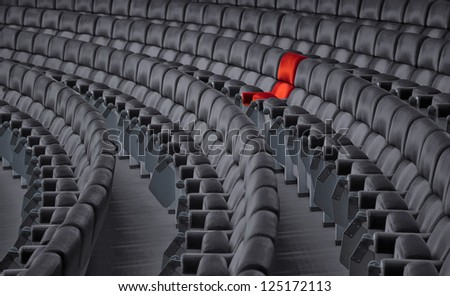 photo with red armchair in grey chair rows - stock photo