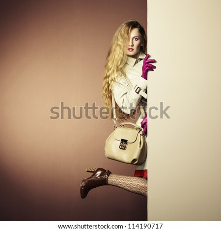 Photo young beautiful woman in a raincoat in interior. Conceptual fashion - stock photo