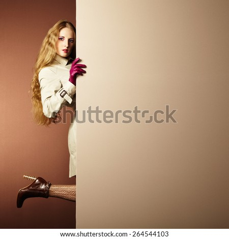 Photo young beautiful woman in a raincoat in interior. Conceptual fashion. Text background - stock photo