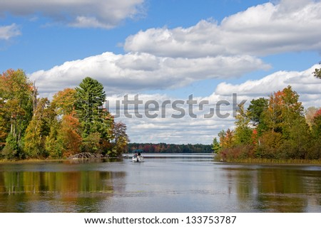 Photograph of a beautiful northwoods lake in the autumn season being enjoyed by a group heading out into the waters on a pontoon boat. - stock photo
