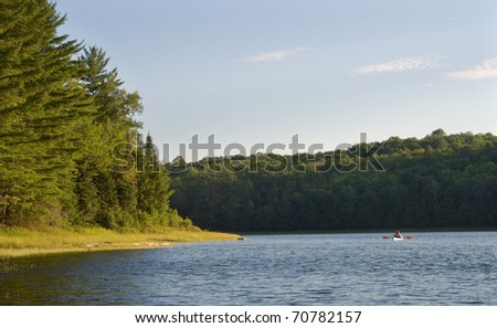 Photograph of a beautiful pristine wilderness lake in the northwoods of Wisconsin, with a kayaker enjoying the beautiful trees lit by the warm light of the evening sky. - stock photo
