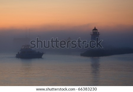 Photograph of a Lake Superior harbor entrance at dawn, before the sun is up, with a fishing boat heading out into the lake past a lighthouse. - stock photo