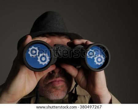 Photograph of a man in trench coat and hat looking through binoculars with reflected symbols in the lenses. - stock photo