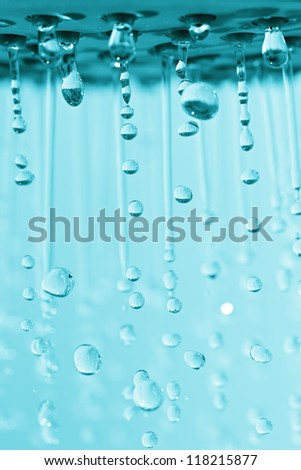 Photograph of a shower head showing drops and streams of water. Blue toned. - stock photo