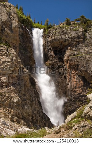 Photograph of a tall and beautiful waterfall high in the mountains of Glacier National Park in northwest Montana. - stock photo