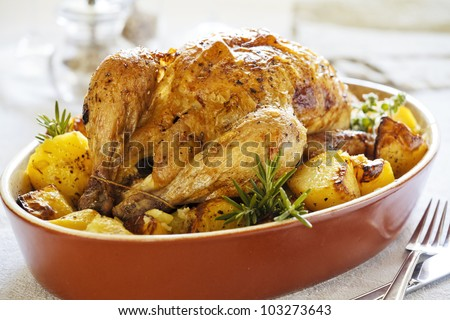 Photograph of a tasty roasted chicken with potatoes - stock photo