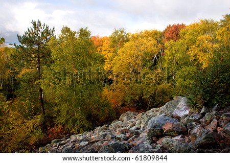 Photograph of an area of rock slide in a state park on Rib Mountain in north-central Wisconsin.  Taken during the peak of the autumn season with beautiful vibrant colors. - stock photo