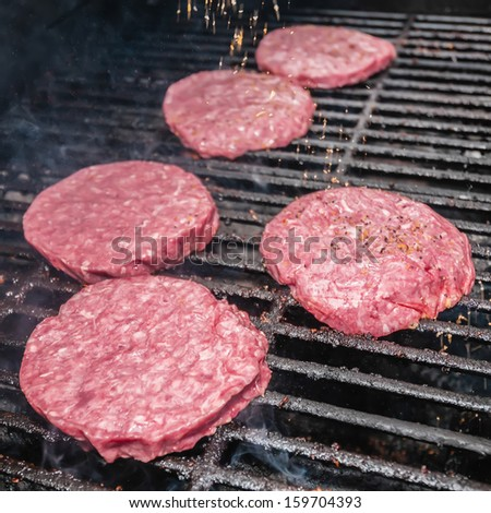 Photograph of   tasty beef burgers on the grill - stock photo