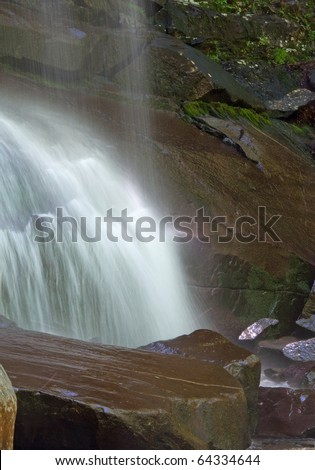 Photograph of the bottom of Rainbow Falls in Smoky Mountain National Park.  Shot with an extended exposure to soften the water and give it a smooth bridled effect. - stock photo