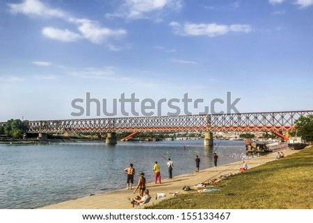 Photograph of The Old railroad truss bridge, with the group of hobbyist anglers in the foreground, and the Gazelle bridge in the background, on Sava river, Belgrade, Republic of Serbia. - stock photo