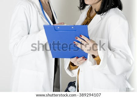 photograph of two female doctor who consult a medical chart - stock photo