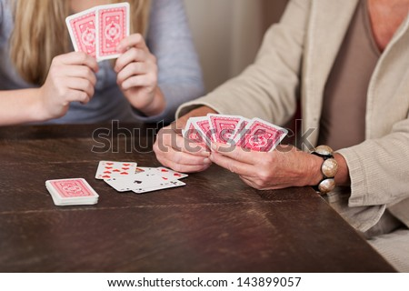 Photograph of two females playing cards together. - stock photo