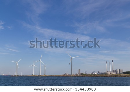 Photograph of wind power plants and industrial buildings in Copenhagen, Denmark. - stock photo