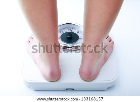 Photograph showing a woman on a bathroom scale close-up - stock photo