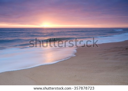 Photograph taken at sunset during Autumn season in Praia do Trafal (Algarve Portugal). It portraits calm beach waves coming ashore - stock photo