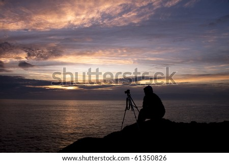 Photographer at sunset - stock photo