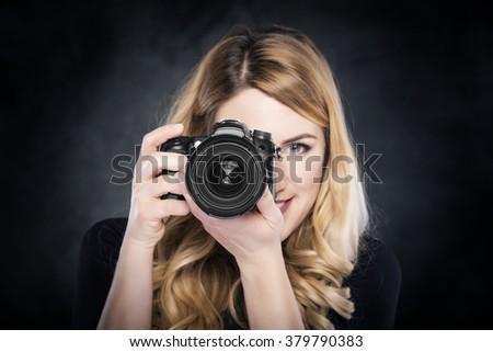 Photographer blond woman holding camera over dark background. - stock photo