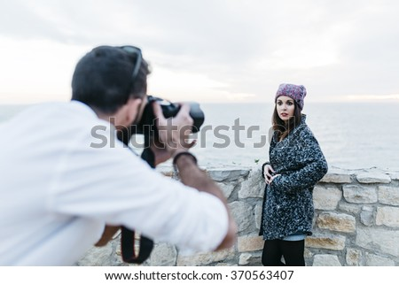 Photographer doing a photo shoot at a model - stock photo
